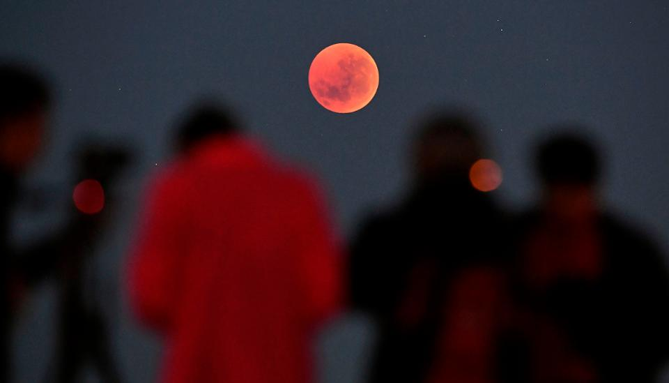 People gather to watch a ″blood moon″ eclipse in Melbourne on July 28, 2018. (Photo by WILLIAM WEST / AFP)