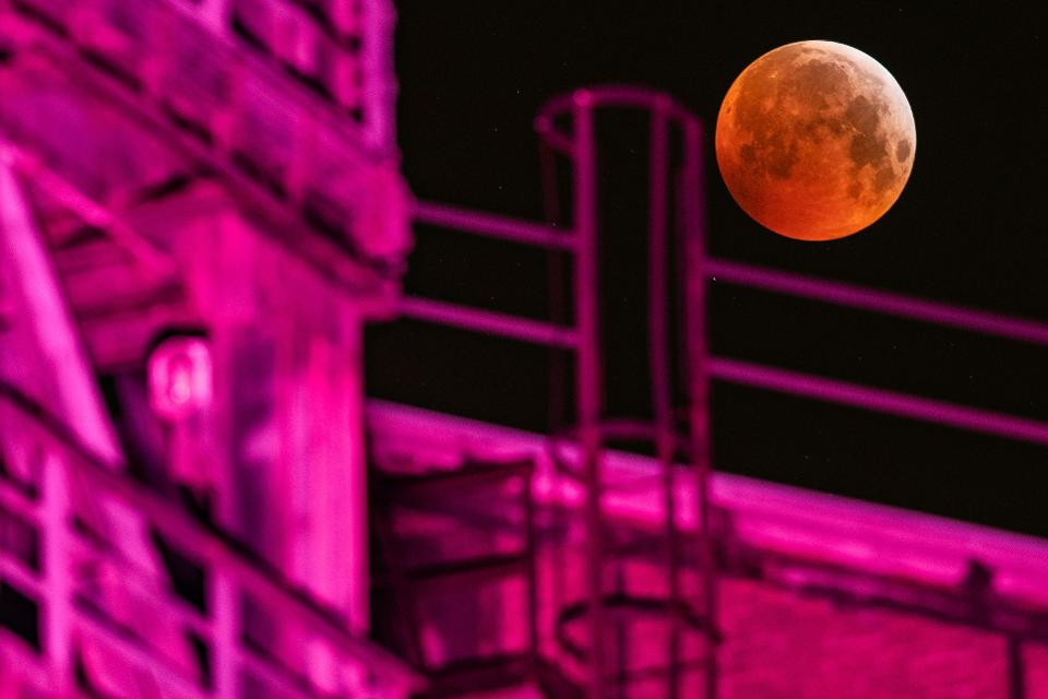 A picture taken on January 21, 2019 in Duisburg shows a view of the Super Blood Moon above an industrial plant during a lunar eclipse. (Photo by Marcel Kusch / dpa / AFP)